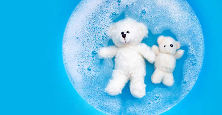 Soak toy bear in laundry detergent water dissolution before washing.  Laundry concept, Top view