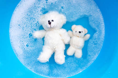 Soak toy bears in laundry detergent water dissolution before washing.  Laundry concept, Top view Stock fotó