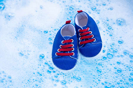 Soak baby shoes in baby laundry detergent water dissolution before washing.  Laundry concept, Top view Stock fotó