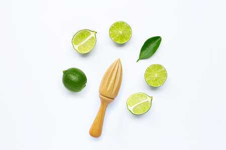 Fresh lime with wooden juicer on white background. Copy space
