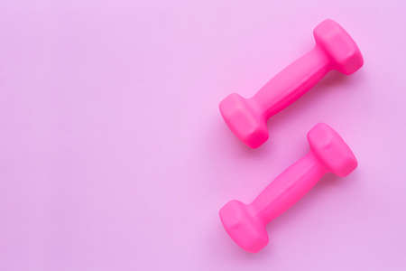 Top view of pink dumbbells isolated on pink background. Copy space Stock Photo