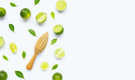 Fresh limes and leaves with wooden juicer on white background. Copy space