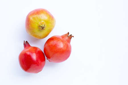 Top view of ripe pomegranate fruit on white background.