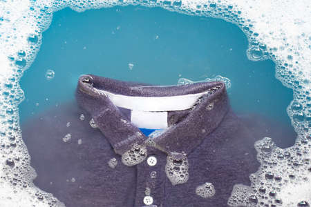 Polo shirt soak in powder detergent water dissolution, washing cloth. Laundry concept