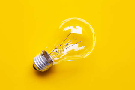 Light bulb on yellow background. Top view Stock Photo