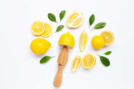 Fresh lemon and leaves with wooden juicer on white background. Stock Photo