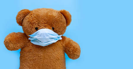 Teddy bear with mask on blue background. Copy space