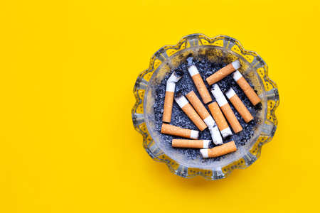 Smoked cigarettes on yellow background. Copy space Stok Fotoğraf