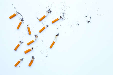 Cigarette butts and ashes on white background. Copy space