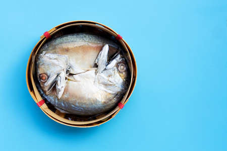 Short mackerel in fish basket on blue background. Top view with copy space