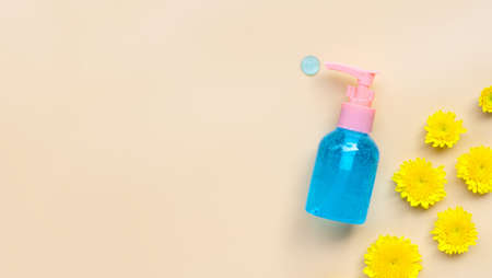 Alcohol hand sanitizer gel in pump bottle with yellow flower on cream color background. Copy space