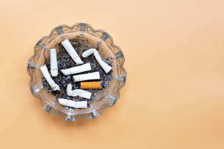 Smoked cigarettes on cream color background. Copy space