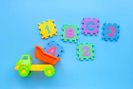 Colorful toy with english alphabet and numerals on blue background. Education concept, Copy space