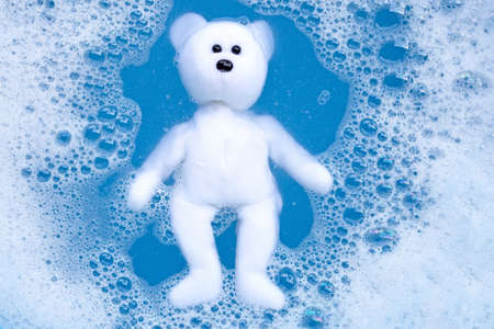Soaking bear toy in laundry detergent water dissolution before washing. Laundry concept, Top view