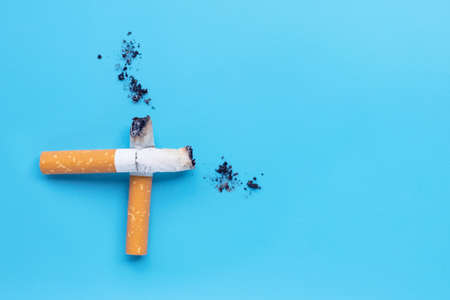 Cigarette butts and ashes on blue background. Copy space Stok Fotoğraf