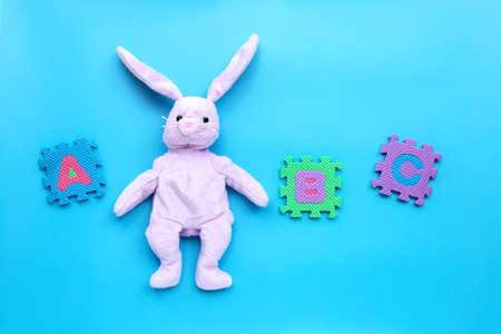 Rabbit toy with english alphabet puzzle on blue background. Education concept, Copy space