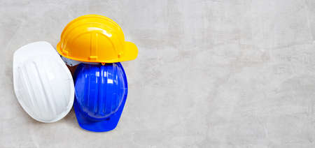 Construction helmets on concrete background. Top view