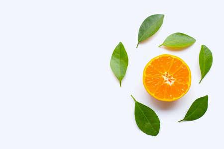 Fresh orange citrus fruit with green leaves on white background.