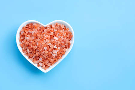 Pink himalayan salt in heart shape bowl on blue background. Copy space Stock Photo