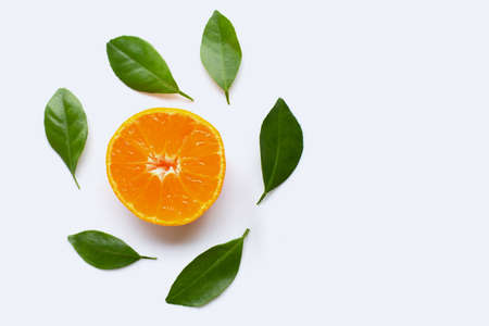 Fresh orange citrus fruit with green leaves on white background.