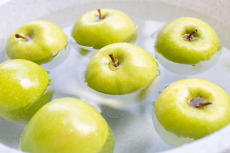 Soak green apple in water. Washing fruit concept