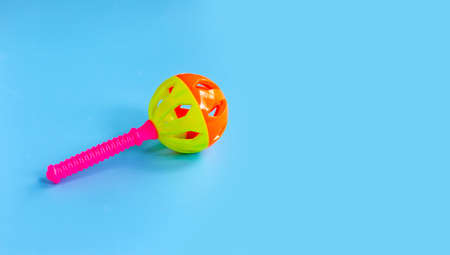 Colorful baby rattle on blue background. Copy space Archivio Fotografico