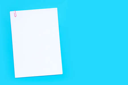 White paper with paperclip on blue background. Copy space