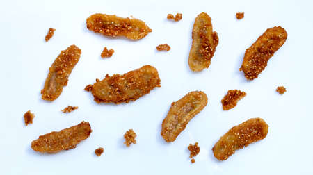 Fried bananas with sesame seeds on white background.  Top view