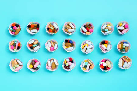 Colorful tablets with capsules and pills in cupcake wrappers on blue background.