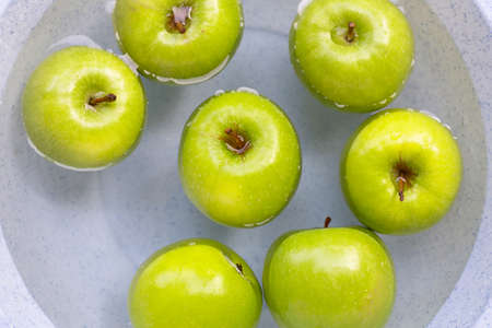 Soak green apples in water. Washing fruit concept. Top view