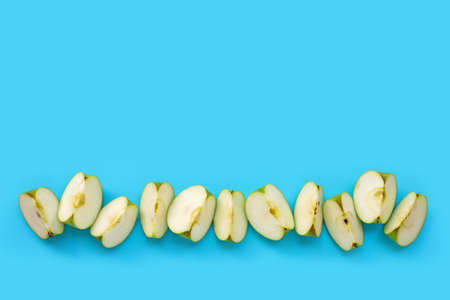 Green apple slices on blue background. Copy space Imagens