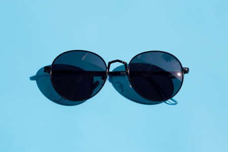 Sunglasses on blue background. Enjoy holiday concept. Copy space Imagens
