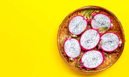 Ripe dragonfruit or pitahaya in wooden bamboo threshing basket on yellow background. Copy space Imagens