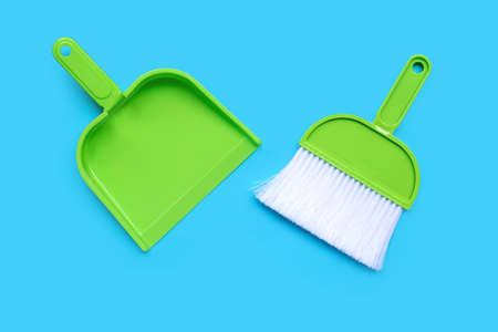 A broom and dustpan on blue background.