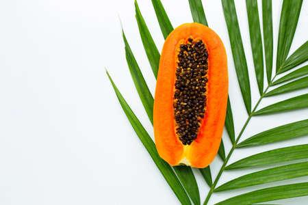 Sweet ripe papaya on tropical palm leaves. Top view Imagens