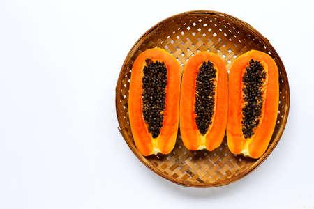 Ripe papaya fruit in wooden bamboo threshing basket on white background. Copy space Imagens