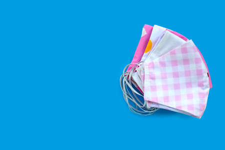 Handmade colorful cloth masks on blue background. Copy space