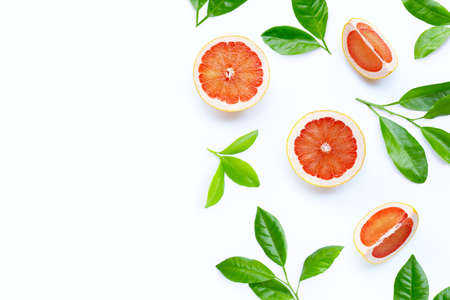 High vitamin C. Juicy grapefruit slices with green leaves on white background. Copy space