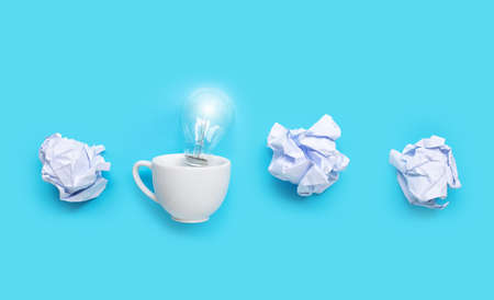 Light bulb in white cup with white crumpled paper balls on blue background. Ideas and creative thinking concept. Copy space Imagens