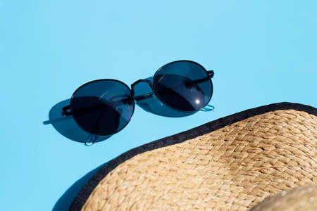 Sunglasses with summer hat on blue background. Enjoy holiday concept. Copy space