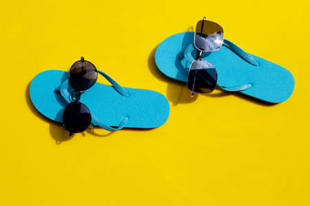 Blue flip flops with sunglasses on yellow background. Enjoy summer holiday concept.