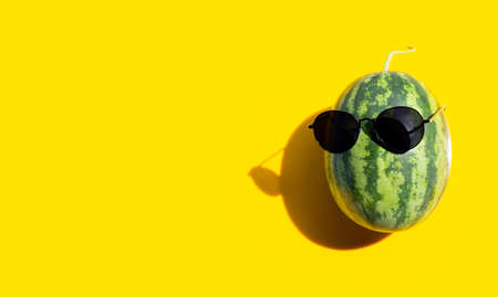 Watermelon with sunglasses on yellow background. Enjoy summer holiday concept. Copy space