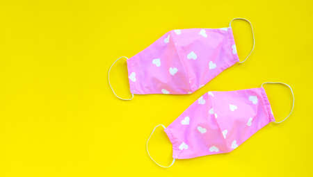 Handmade pink and heart shape cloth masks on yellow background. Copy space Archivio Fotografico