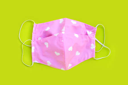 Handmade pink and heart shape cloth masks on green background. Copy space