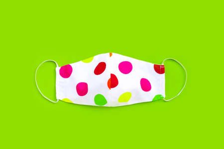 Handmade colorful cloth mask on green background. Top view Imagens