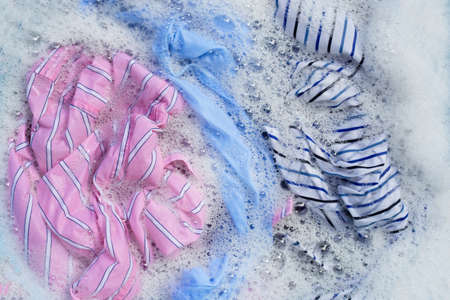 Top view of color clothes soak in powder detergent water dissolution. Laundry concept