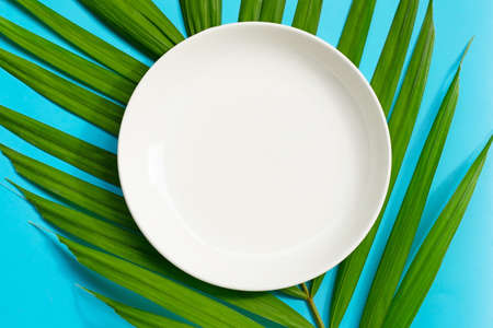 Empty white ceramic plate on tropical palm leaves on blue background. Top view