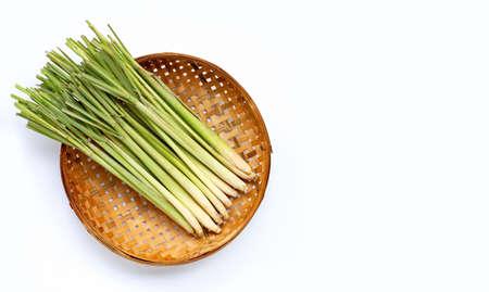 Fresh lemongrass in wooden bamboo threshing basket on white background. Copy space
