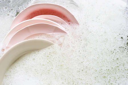 Washing dishes, Close up of utensils soaking in kitchen sink.