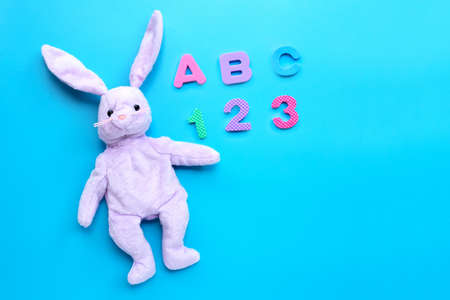Rabbit toy with english alphabet puzzle and numerals on white background. Education concept, Copy space